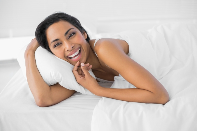 shutterstock_160528004 woman laughing in bed Feb15