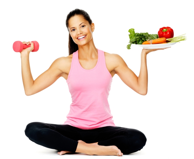 WOman holding a weight in one hand and plate of fruit and veg in the other