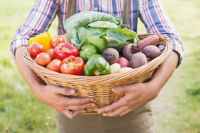 close upof woman carrying basket of in season fruit and vegetables