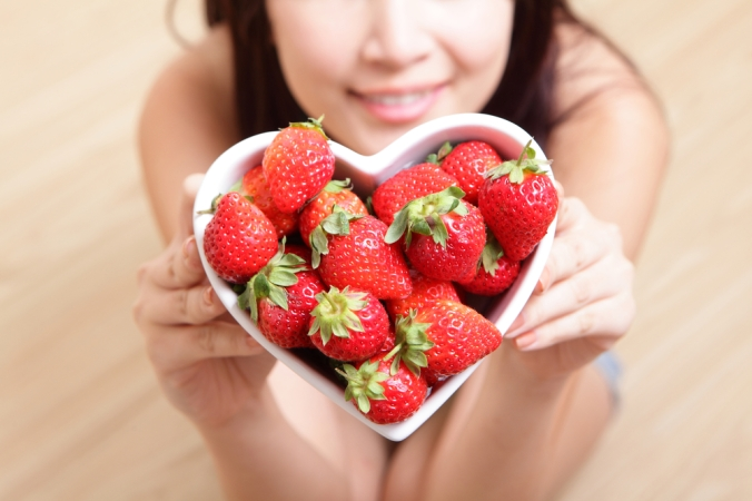 A woman holding a heartshaped bowl full of strawberries