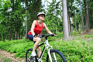 shutterstock_144420346 woman cycling in forest Sept15