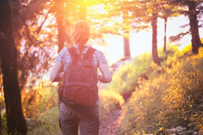 A woman wiht a rucksack enjoying a walk outdoors in a forest
