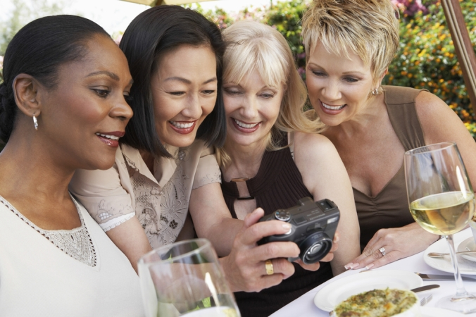 A group of women in their 50's looking at a photo on the screen of a camera