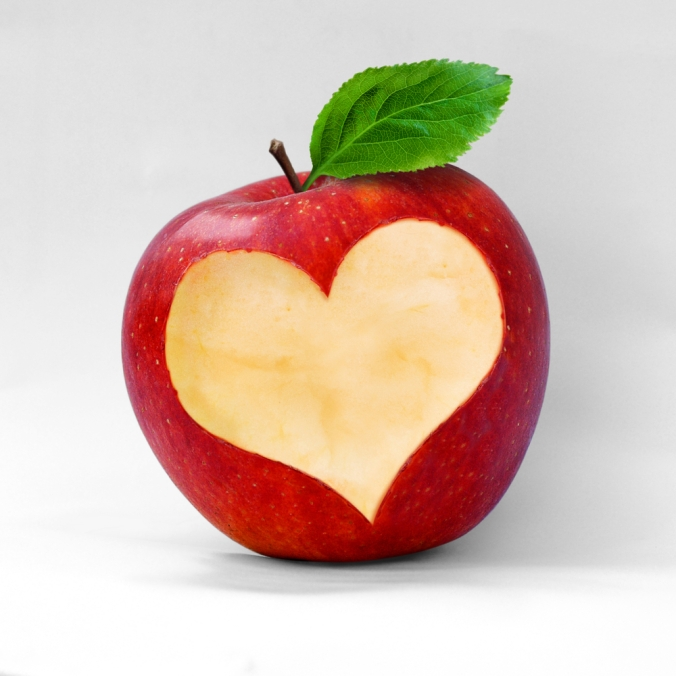 An apple with a heart shape cut out to show that apples are good for a healthy heart