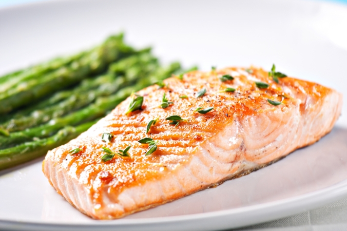 Salmon fillet and asparagus on a white plate