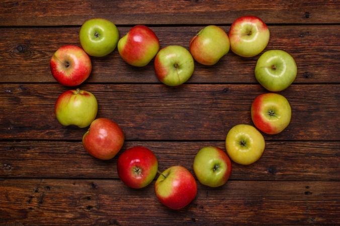 Apples made into a heart shape on a wooden background