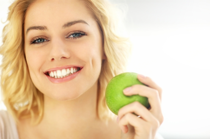 Close up of a happy young woman holding an apple