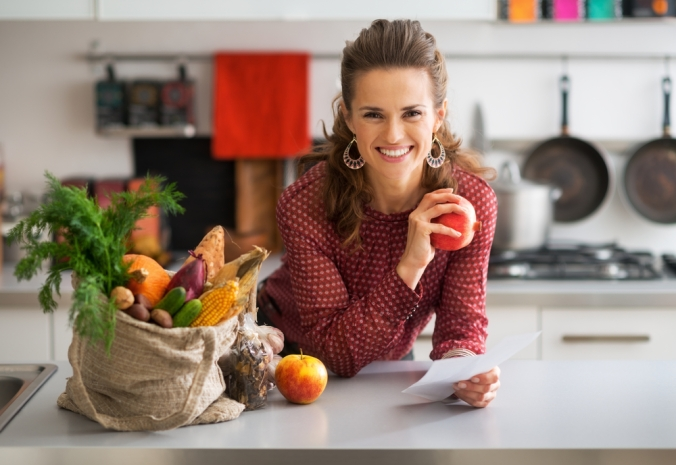 Close up of woman in kitchen with bwon bag of organic fruit and veg