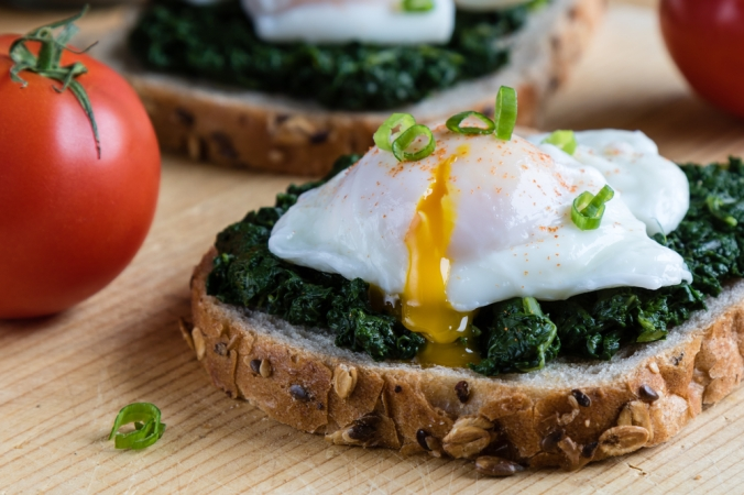 POached egg on wilted spinach on rye bread