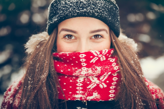 Close up of woman with wooly hat and scarf to represent winter