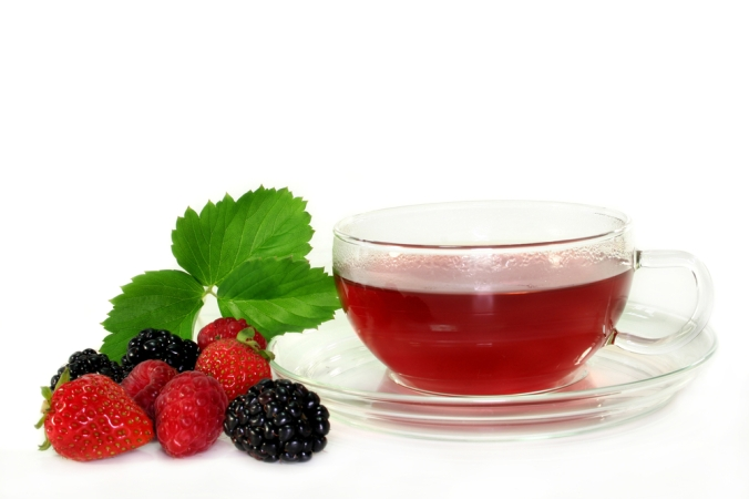 Fruit tea with berries next to a cup
