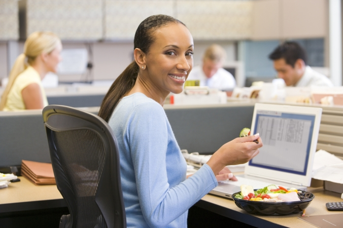 Happy woman at desk eating her lunch