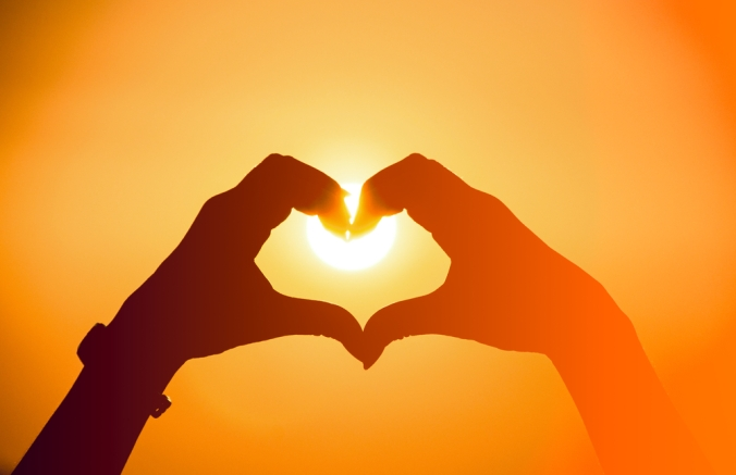 CLose up of two hands making a heart shape with the sun in the background