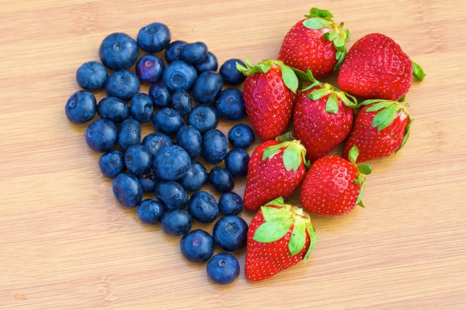 Blueberries and strawberries in a heart shape on a wooden board