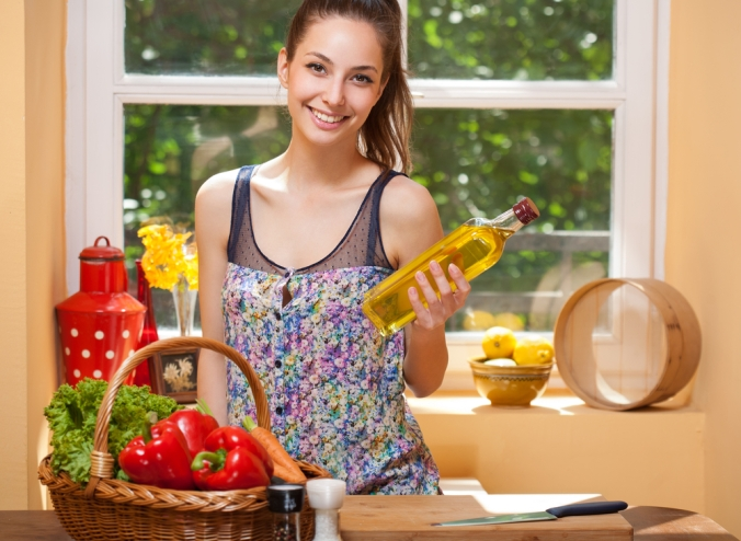 Woman in kitchen holding bottle of olive oil wutg basket of peppers on work surface