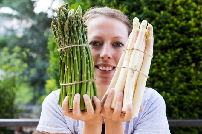 A woman holding a bunch of green asparagus and a bunch of white asparagus