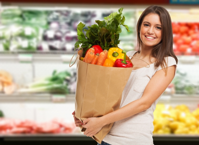 Happy woman holding a brown paper bag of vegetables in her kitchen