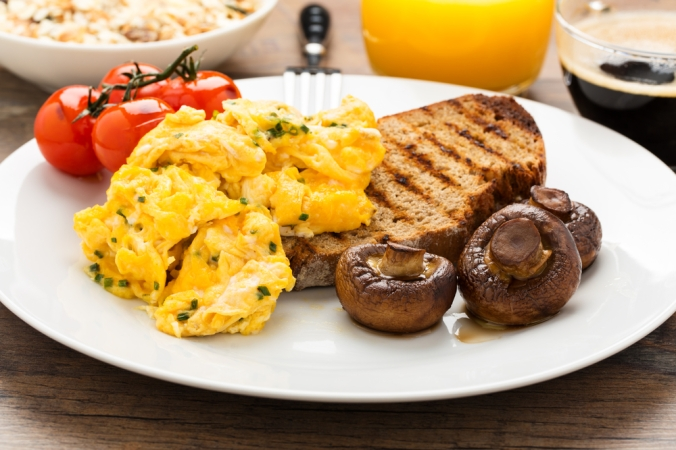 Scrambled egg breakfast with toast, tomatoes, mushrooms and a glass of orange juice