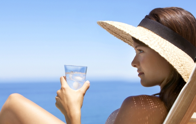 Close up of woman on beach with a glass of water to represent hydration