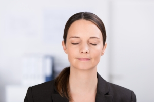 shutterstock_163796705 woman deep breathing relaxing office July16