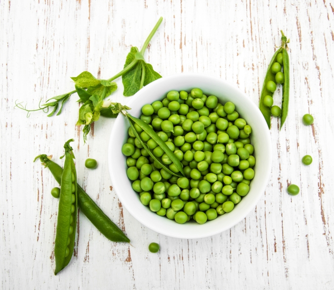 a bowl of fresh peas and pea pods on a table