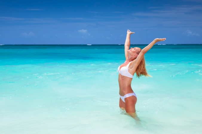 Woman in bikini standing in the sea with her arms in the air to represent a happy holiday