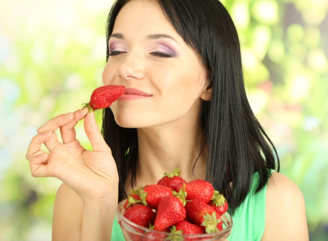Woman smiling with a bowl of strawberries, holding on strawberry up to her mouth