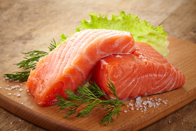 Two fillets of salmon on a wooden board