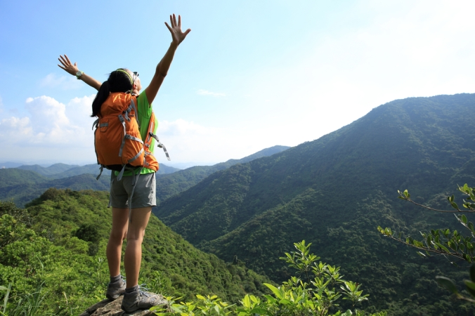 A woman out for a walk in the hills with her arms outstretched enjoying herself