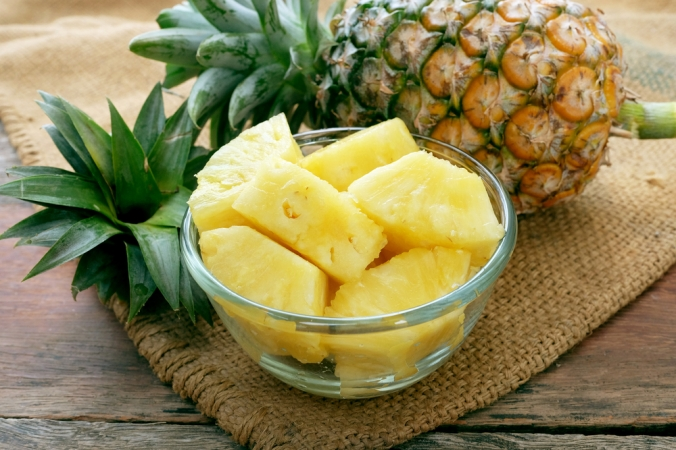 A bowl of cut up lineapple next to a whole pineapple