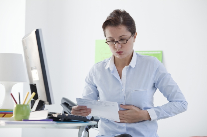 shutterstock_173838809 woman at work desk indigestion Sept16