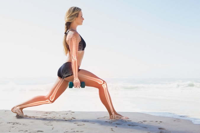 Woman lunging on a beach with the outline of her bones shown as if x-rayed to represent strong bones