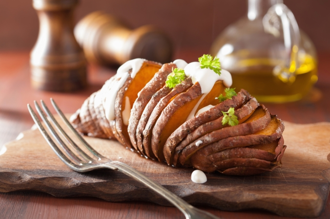 A sweet potato cut in hasselback style on wooden board