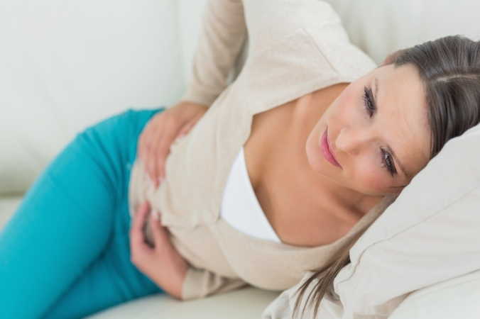shutterstock_119446654-woman-lying-on-sofa-tummy-pain-oct16
