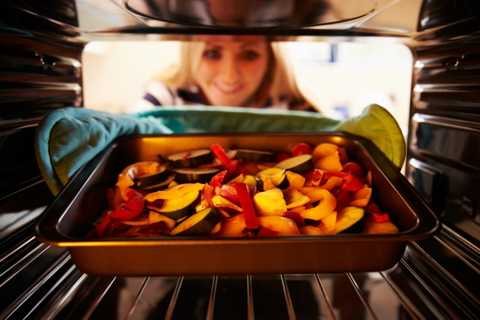 A woman taking a tray of roasted vegetables out of the oven