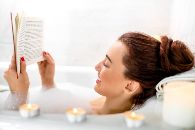 CLose up of a woman relaxing in the bath reading a book, surrounded by candles