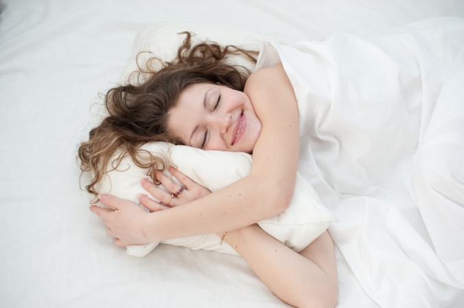 Happy woman sleeping, cuddling pillow and smiling