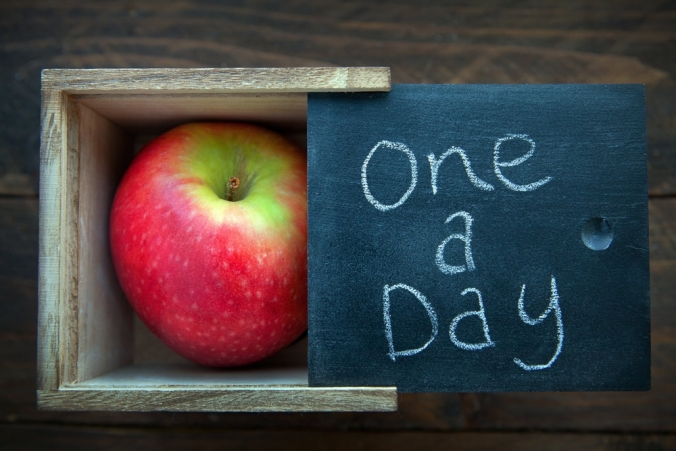 An apple in a box with 'one a day' written on the lid