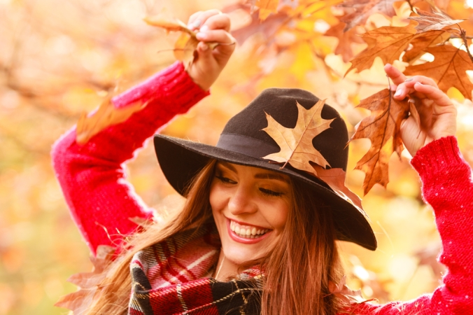 Happy woman in autumn playing with autumn leaves