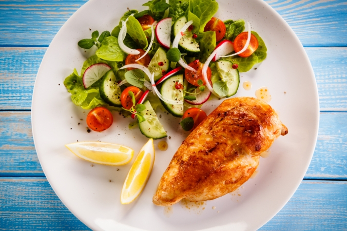 Chicken breast with side salad representing balanced meal