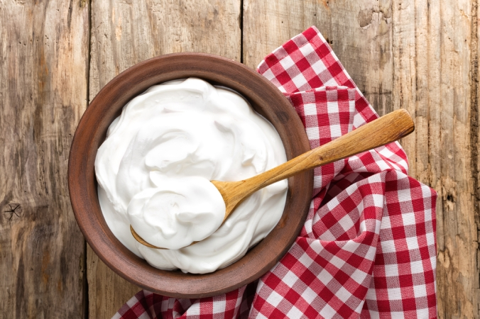 A bowl of natural yoghurt on a wooden background