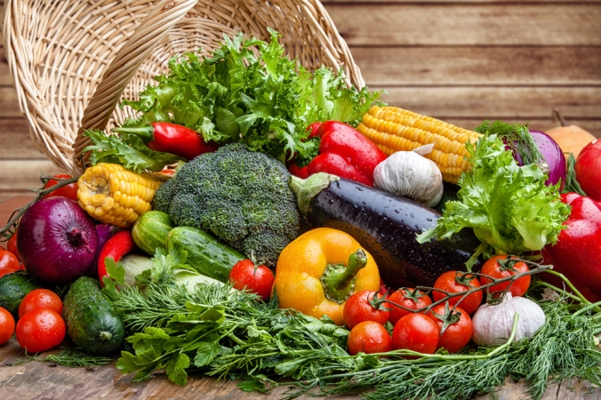 A range of vegetables on a wooden background