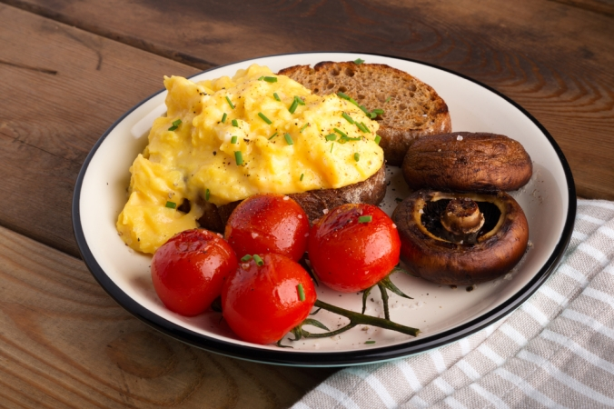 Scrambled eggs on toast with mushrooms and tomatoes