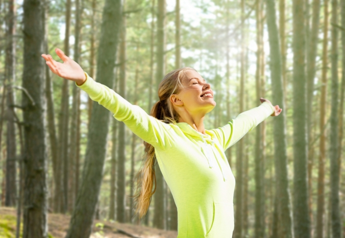 Close up of woman with arms outstretched, smiling in a forest