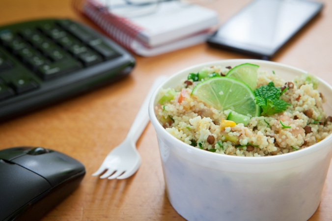 Tub of quinoa salad on a desk with keyboard and mouse in background