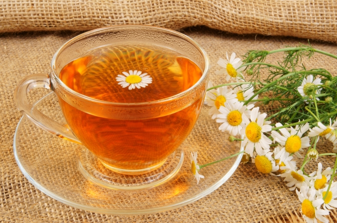 A cup of camomile tea and camomile flowers next to it