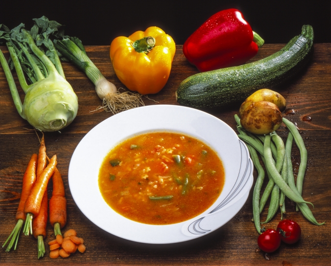 A bowl of vegetable soup surrounded by vegetables