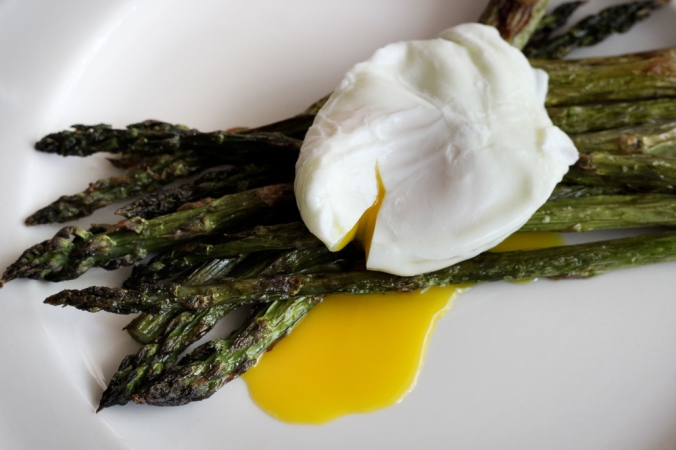 A poached egg on top of steamed asparagus to show a healthy breakfast
