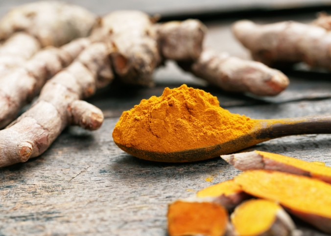wooden spoon with powered turmeric and turmeric root