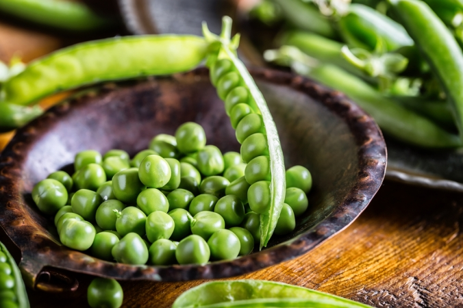 A bowl of fresh green peas and a pea pod